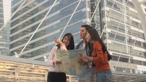 vidéos et rushes de amis en regardant carte - montrer la voie