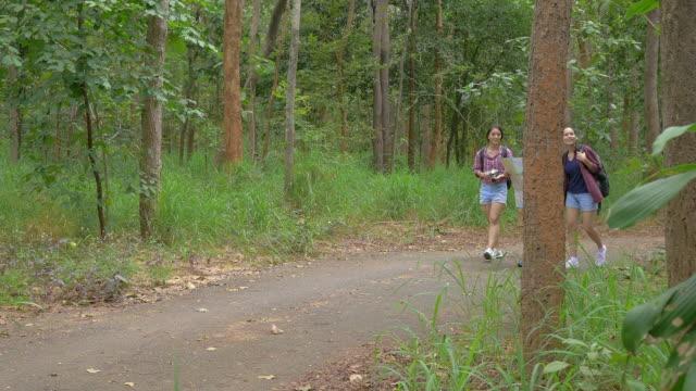 Vrienden op zoek kaart en wandelen in het bos. Aziatische mannen en vrouwen reizen buiten levensstijl in bos