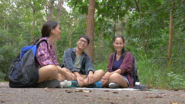 Vrienden op zoek kaart in bos. Aziatische mannen en vrouwen reizen buiten levensstijl in bos
