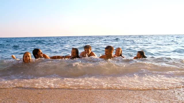 vídeos de stock, filmes e b-roll de slo mo amigos deitado em águas rasas - raw footage