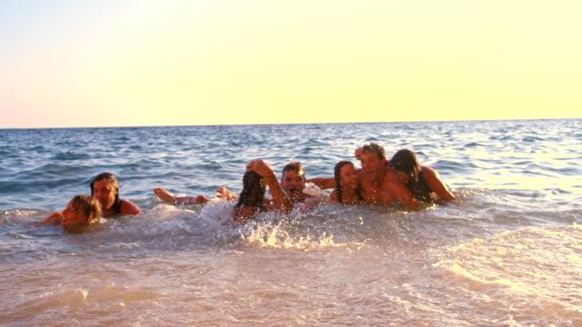 vídeos de stock e filmes b-roll de slo mo amigos deitada na água raso - 20 24 anos