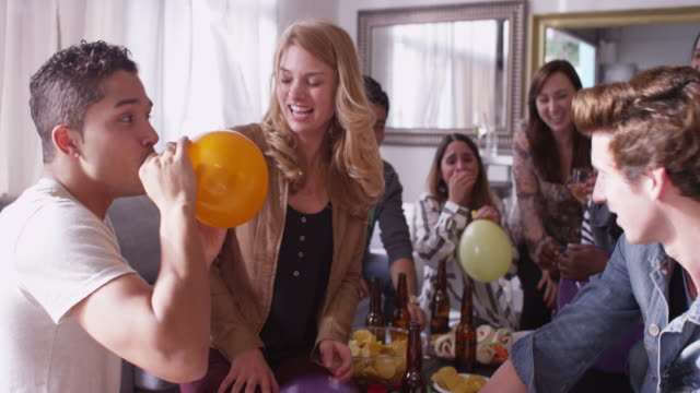 friends making each other laugh with helium balloons at party - helium stock videos & royalty-free footage