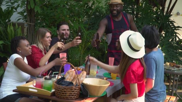 vídeos y material grabado en eventos de stock de amigos haciendo tostadas y disfrutando de la comida juntos al aire libre - happy meal