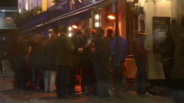 friends meet and socialise outside a traditional english pub - happy hour video stock e b–roll