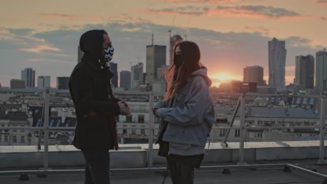 vänner möte under pandemi av coronavirus. prata och beundra solnedgång på taket - social gathering bildbanksvideor och videomaterial från bakom kulisserna