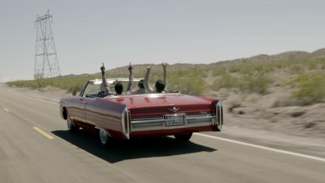 Friends on desert road trip in classic convertible throw hands up, high-five, and cheer