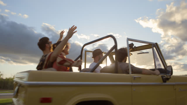 Friends on road trip in classic Bronco convertible throw hands in the air