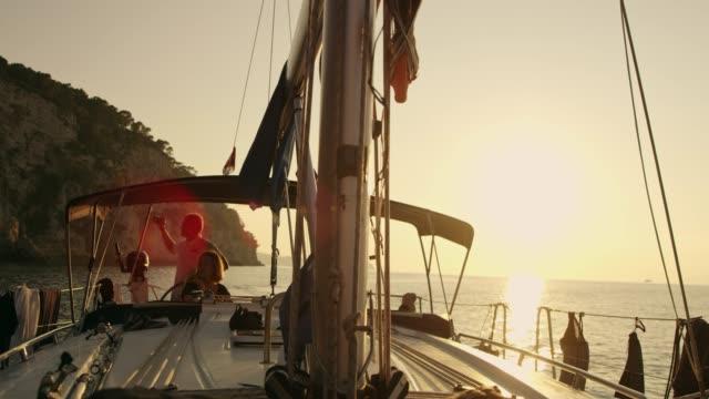 vídeos y material grabado en eventos de stock de amigos en velero en el océano de sol, puesta del sol, cámara lenta - idílico