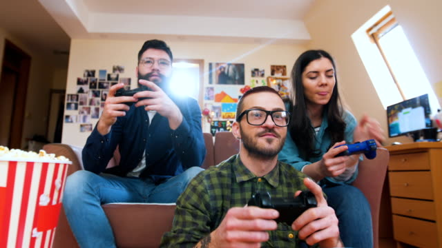 Friends on sofa playing games console