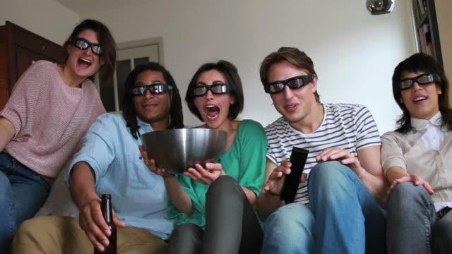 vídeos de stock, filmes e b-roll de os amigos no sofá assistir televisão com óculos 3d - óculos de terceira dimensão