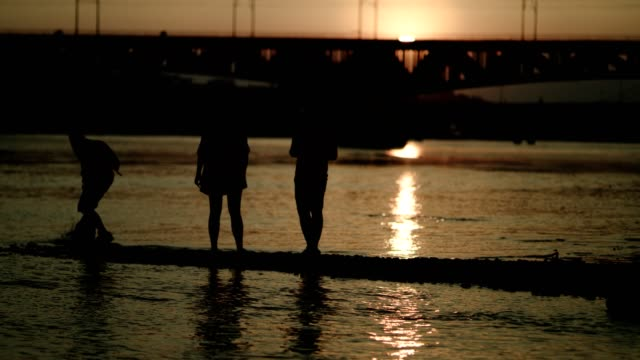 friends on urban beach. industrial area. sunset silhouettes - riverbank stock videos & royalty-free footage