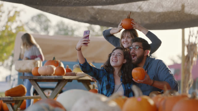 friends pick out pumpkins together and take selfies at a farmers market - out take stock videos & royalty-free footage