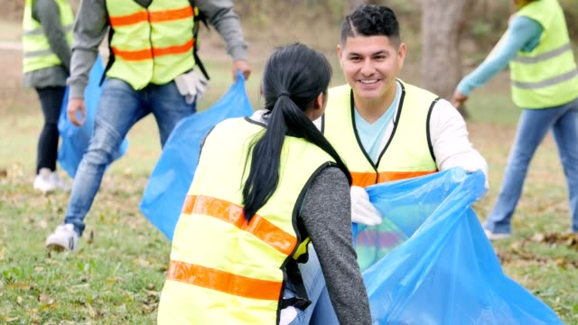 Friends pick up garbage together during community cleanup day