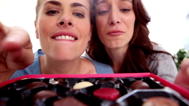 friends picking chocolates from a box - indulgenza video stock e b–roll
