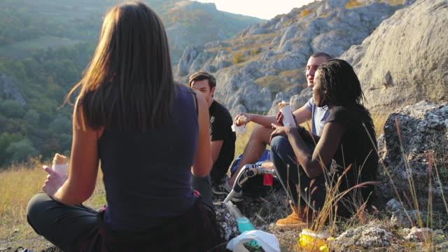 vidéos et rushes de les amis pique-niquent ensemble à l'heure d'été. loisirs inclusifs - picnic