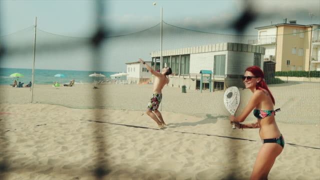 friends play beach tennis and have fun - racket stock videos and b-roll footage