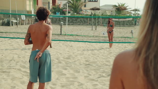 Friends play beach tennis and have fun