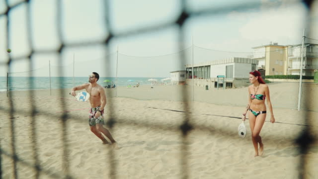 vídeos de stock e filmes b-roll de friends play beach tennis and have fun - raqueta