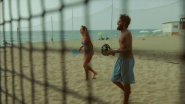 Freunde spielen Beach-Tennis und Spaß haben