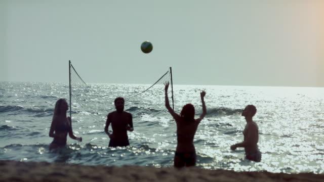 Freunden Beachvolleyball spielen und Spaß haben