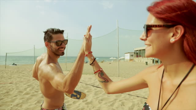Friends play beach volley and high five