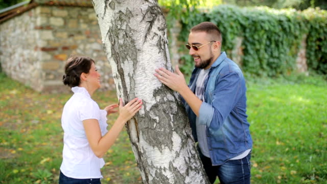 friends play hide-and-seek around the tree. - hide and seek stock videos and b-roll footage