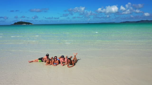 friends play in the turquoise waters and white silica sand beaches of whitehaven beach. - braun stock-videos und b-roll-filmmaterial