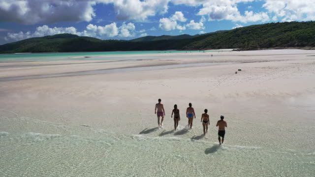 Friends play in the turquoise waters and white silica sand beaches of Whitehaven Beach.