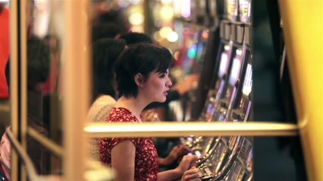 vídeos y material grabado en eventos de stock de friends play slot machines in vegas casino, young woman gets frustrated and excited - máquina con ranura