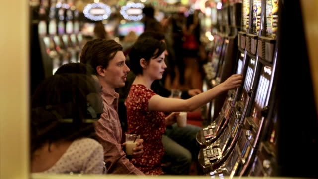 Friends play slots in Las Vegas casino, young guy wins big
