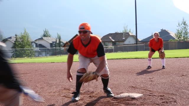vídeos y material grabado en eventos de stock de los amigos juegan softball en el campo de béisbol designado - sófbol