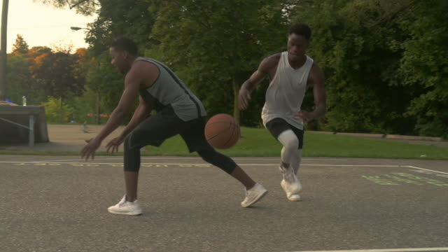vidéos et rushes de friends playing basketball together outdoors in early morning. - joueur de basket ball