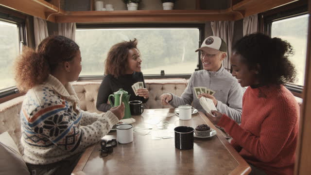 friends playing cards while spending leisure time in camper van - luck stock videos & royalty-free footage