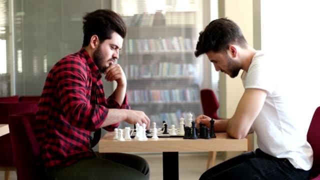 stockvideo's en b-roll-footage met vrienden samen schaken - spelletjesavond