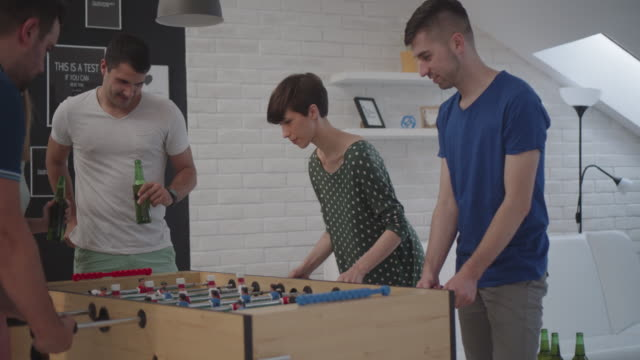 Friends Playing Foosball At Home.