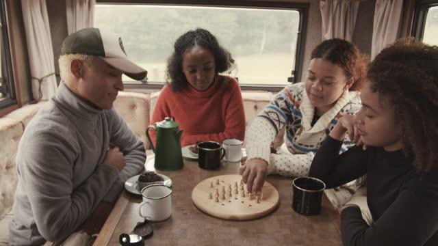 friends playing game in camper van - board game stock videos & royalty-free footage