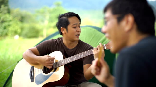 Friends playing guitar and singing in camping with tent background
