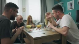 Friends playing in strategic Board Game with cards and dice in cozy living room