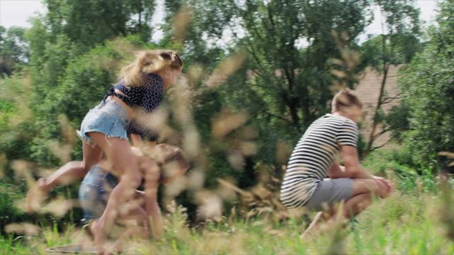 vídeos de stock, filmes e b-roll de friends playing leapfrog - jogo de carniça