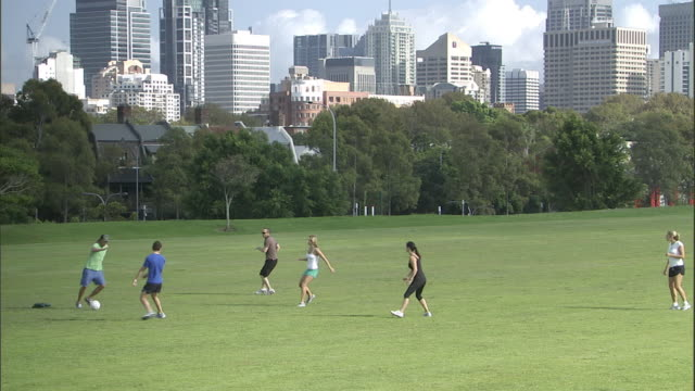 WS, PAN, Friends playing soccer in park, Sydney, Australia