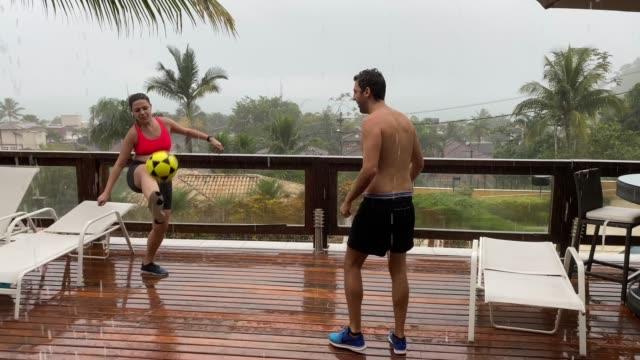 freunde spielen fußball im regen am strandhaus - freizeitaktivität stock-videos und b-roll-filmmaterial