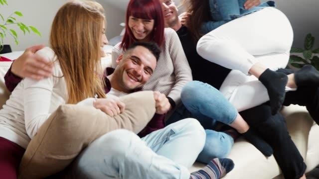vídeos y material grabado en eventos de stock de amigos jugando juntos en el sofá en casa - lucha con almohada