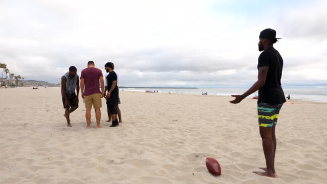 ws friends playing touch football on beach on summer evening - touch football video stock e b–roll