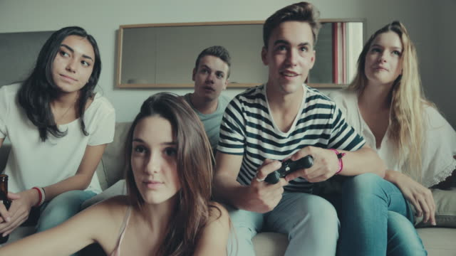 friends playing videogames at home slowmotion - gamepad stock videos & royalty-free footage