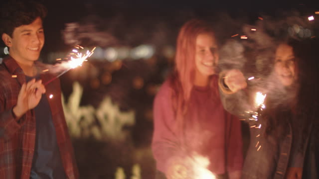 vidéos et rushes de friends playing with fireworks at night - nouvel an