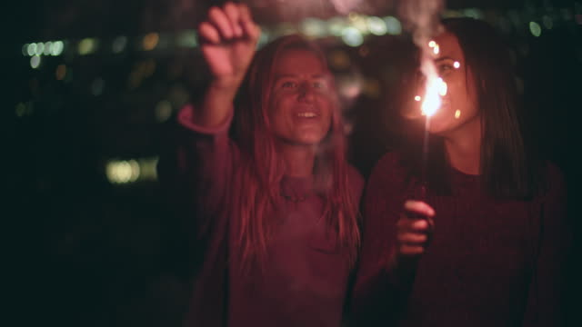 cu friends playing with sparklers at night - weiblicher teenager stock-videos und b-roll-filmmaterial