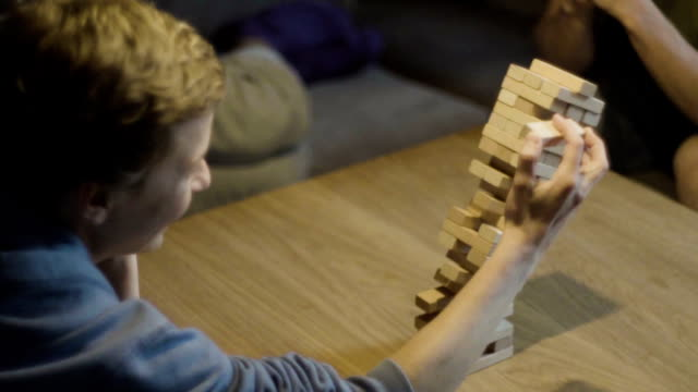friends playing with the wood game. risk metaphore - rischio video stock e b–roll
