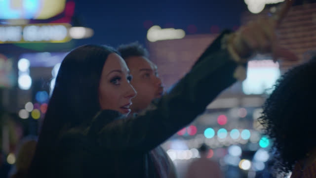 friends point up at the sights on the las vegas strip at night. - three people stock videos & royalty-free footage