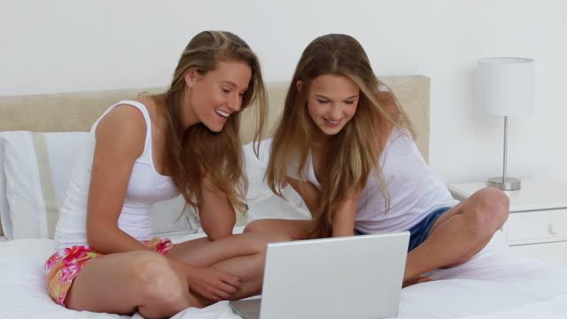 vidéos et rushes de friends pointing together at a laptop - prendre sur les genoux