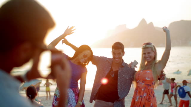 Friends pose at sunset for smartphone photos on the beach at Ipanema